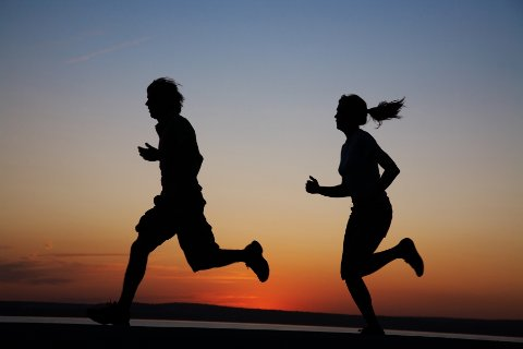The man and the woman run together on a sunset on lake coast