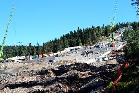 BYGGER OVENFRA: Byggingen av rammeverket for veggene og taket til skihallen Snø er i gang øverst i bakken, såvidt innenfor markagrensa i Gjelleråsmarka. Konturene av gigantprosjektet synes nå godt både for forbipasserende på E6 og fra Lørenskogveien. (Se dronevideo litt lenger ned i saken)