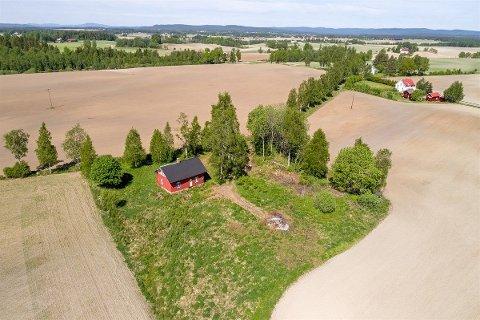 LANDLIG IDYLL: Eiendommen med det lille huset er omkranset av jorder.