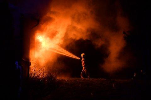 Her jobber en av brannvesenets mannskaper med å få kontroll på de voldsomme flammene.