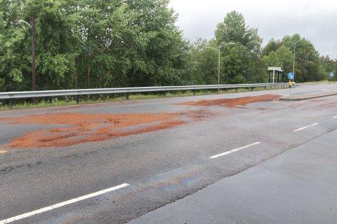 TØRKES: Brannvesenet har lagt store mengde sagflis i veibanen for å fjerne oljesølet.