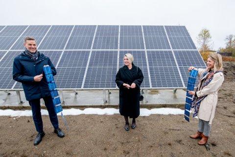 Olje- og energiminister Marte Mjøs Persen klipper et bånd med solceller for å markere åpningen av IFEs testanlegg for solcellemoduler.