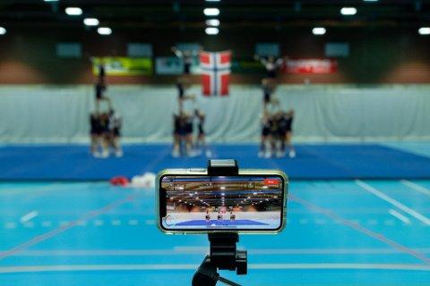 Spesiell dommer: Opptaket fra denne mobiltelefonen vil være det dommerne skal se når de avgjør hvor godt NRC Tigers fire lag med cheerleadere vil gjøre det i VM. Nyvinningen ble brukt da de norske utøverne hadde sine gjennomføringer i Skedsmohallen lørdag til mandag.