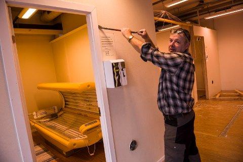 Finn Andersen går løs på inventaret med brekkjernet. Før 1. januar skal alt av solariumsbåser, dører og innredning være borte.