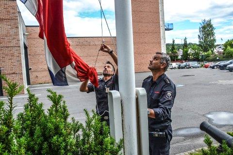 FOR DRONNINGEN: Brannkonstabel Tor Henrik Norberg (t.v.) og brannmester Willy Morten Jørgensen heiser flagg på brannstasjonen i anledning Dronning Sonjas 80-årsdag.