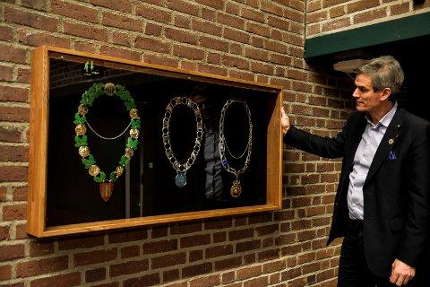 PÅ VEGGEN: Nå henger de gamle ordførerkjedene i glass og ramme, på veggen i bystyresalen.