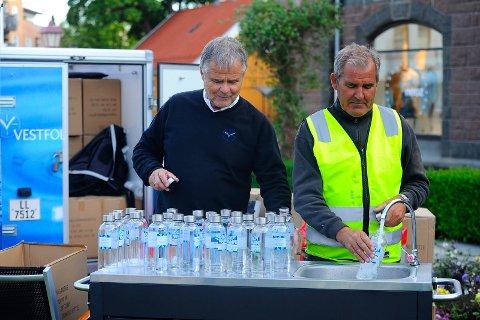 VANN TIL PUBLIKUM: Roy Bjelke fra Vestfold Vann fikk hjelp fra arrangørklubbens Geir Olafsen med å fylle flasker som de delte ut til publikum under fredagens gateritt.