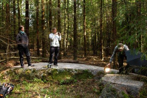 UVANLIG: Inne i Krokenskogen gjorde arkeologene et uventet funn da de var ute på en registreringsjobb. Katrine Fimreite (lys genser) gjorde et funn på første mulige sted: En stein full av skålgroper, som de her fotograferer. Til venstre står arkeolog Vibeke Lia, mens Magnus Tangen fra Kulturhistorisk museum lyser opp steinen. (Foto: Kulturarv i Vestfold fylkeskommune)