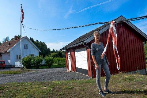 I FLAGGSTANGA: Jorunn Svendsen er fortvilet over en provisorisk strømledning som ligger langs bakken og henger i flaggstanga.