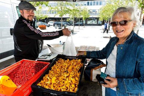 SELGER I POSE OG SPANN: Torvhandler Halvord Kristiansen selger sopp og bær på Torvet i Sandefjord. Her er det Anne markmanrud som sikrer seg en pose tyttebær til middagene fremover.