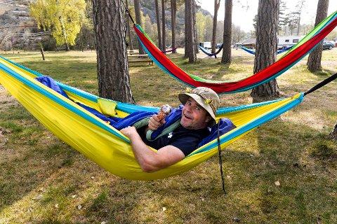 FARGERIKE: Bestyrer Roger Sørsdal, også kalt Kongen av campingplassen prøveligger en av hengekøyene. Her sverger han til svenskekøya, etter sine mange år i nabolandet. Han kan tilby de fleste farger.