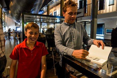 SIGNERTE: Etter foredraget fikk tippoldebarnet Niclas Andersen (12) en signert bok av den argentinske forfatteren Mirko Stopar.