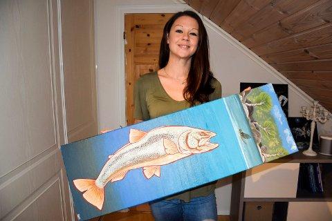 FISKEKUNSTNER: Emma Bäcker-Håkonsen (31) elsker å fiske, og mange av bildene hun står bak bærer preg av denne interessen. Her viser hun fram et ørretbilde hun har malt.