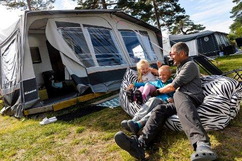 FØRSTEGANGS CAMPERE: Familien fra Bærum var heldige og fikk sikret seg en fast campingplass på Vøra Camping. f.v: Kristina Seres (5), Sondre Seres (10) og Øystein Bergene med sin nye campingvogn i bakgrunn. (Kona og resten av familien hadde tatt seg en tur til Tjodalyng for å plukke bær).