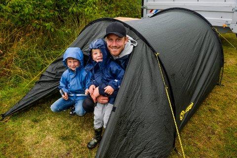 REGN: Morten Skarpenes bor i telt på Asnes sammen med barna Fillip (3) og Bastian (6). De har klart seg fint gjennom nattens regn og fordriver tiden med kortspill. - Det er mulig vi må kjøpe et større telt til neste år, sier far i teltet.