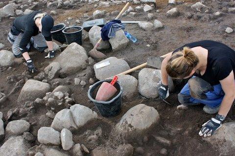 Feltleder Brynhildur Baldursdottir og feltassistent Tanja Larsen graver frem steinene fra steinrøysa.