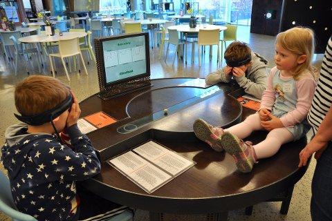 VITENFABRIKKEN: Ada Eline Fjermestad ser på syskenbarna som testar ut hjerneaktiviten på Vitenfabrikken.