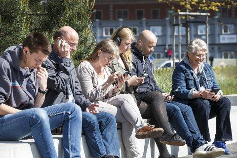 Mobilen tar oppmerksomhet: mange opplever at venner og bekjente er totalt oppslukt i teknologiske duppeditter, og ikke er tilstede i samtalen mellom mennesker. Foto: Scanpix
