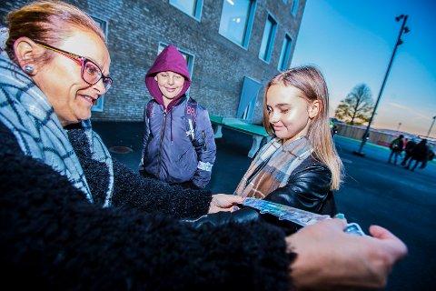 REFLEKS: Ann Kristin Paulsen, miljøarbeider ved Sandesundsveien skole deler ut refleks til Malin Martinsen (t.h.).