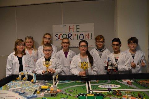 """THE SCORPION: Her poserer de 9 elevene fra Lego League laget """"Nueve Amigos"""" med roboten """"The Scorpion"""" og pokaler fra den regionale finalen. F.v: May-Helene Walther (12), Pernille (12), Sofie Tunæs (12), Andreas Tomta (12), Tiril Andersen (12), Alicia Løken(12), Kristian Laursen (11), Nizar (12), Kjell-Haakon Nøkkelby (12)."""