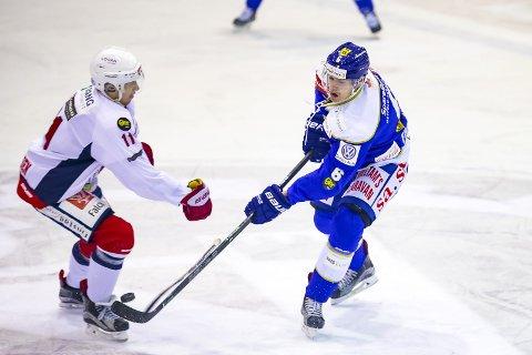 GOD IGJEN: Simon Fredriksson, her i duell med Lørenskog-spiller Olai Sveine Johannessen, var igjen en av Spartas beste spillere. Svensken har funnet tilbake hockeygleden, og det synes også på isen.