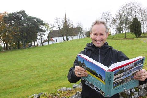 Praktbok om kirker: Lars Ole Klavestad er ute med boken «Kirken i landskapet», som veier 3,3 kilo. Her utenfor Skjeberg kirke, som i arbeidet med boken har skilt seg ut som en av favorittkirkene hans.