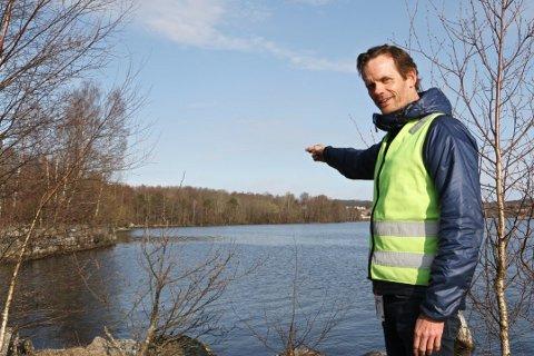 TRYGGERE VANNVEIER: Prosjektleder i Halden kommune, Bjørn Nøstvik, står ved Bjørnstadbrygga og peker over mot Vadet, hvor en av de to nye vannrørene skal strekke seg.
