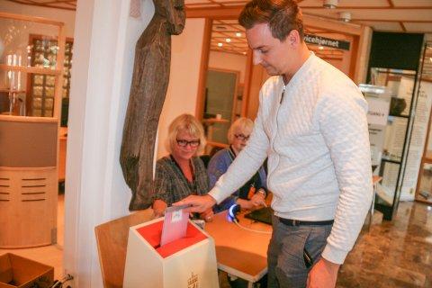 GA SIN STEMME: Thomas Schie (31) legger stemmesedlene i urnen på rådhuset. Valgmedarbeiderne Jannicke Aasen (t.v.) og Anne Slettevold forteller at det har vært en jevn sig i valglokalet de første timene etter det åpnet.  Det er også valgansvarlig Ida Odsæters inntrykk.