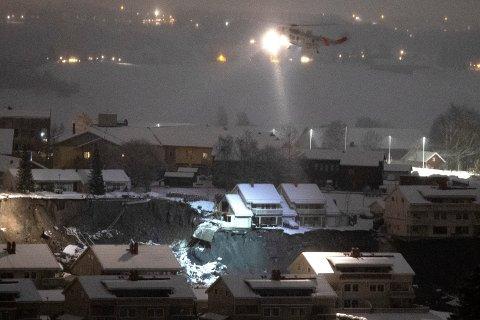 Ask, Gjerdrum 20201231.  Et redningshelikopter over rasstedet i Ask torsdag natt. Letingen etter savnede fortsetter med uforminsket styrke.  Flere boliger ble onsdag morgen tatt av et stort jord- og leirras. Foto: Terje Bendiksby / NTB