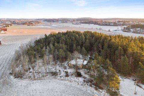 Eneboligen ligger på en liten kolle, omgitt av skog og åkre, med utsikt mot Sarpsborgveien og Lundheim.