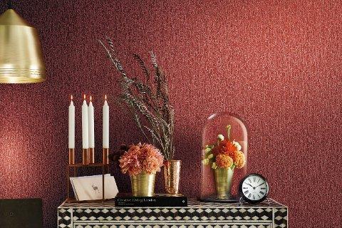Varme farger bidrar uten tvil til å skape en lun atmosfære i stua. Et tapet med tekstur tilfører liv til veggen.