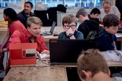 Arne Høyland Ollestad (11 år) i dyp konsentrasjon. Ved hjelp av Arduino skal det lille brettet med alle ledningene han har foran seg lyse opp som et juletre. Nyutdannet elektroingeniør og kodeinstruktør Asbjørn Rørvik hjelper til.
