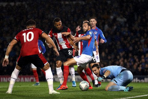 Southampton goalkeeper Alex McCarthy, right, gathers a loose ball in the penalty area during an English League Cup soccer match between Southampton and Portsmouth at Fratton Park, Tuesday, Sept. 24, 2019, in Portsmouth, England. (Andrew Matthews/PA via AP)