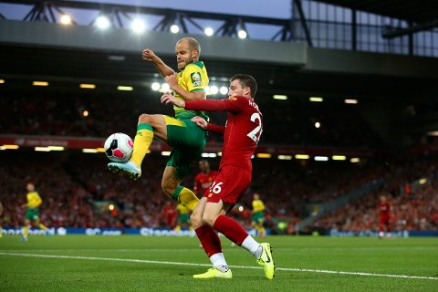 Liverpool's Andrew Robertson, right, and Norwich City's Teemu Pukki fight for the ball during the English Premier League soccer match between Liverpool and Norwich City at Anfield in Liverpool, England, Friday, Aug. 9, 2019. (AP Photo/Dave Thompson)