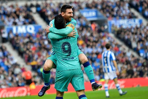 Barcelona's Luis Suarez celebrates with Lionel Messi, top, after scoring his side's second goal during the Spanish La Liga soccer match between Real Sociedad and Barcelona, at Anoeta stadium, in San Sebastian, Spain, Saturday, Dec. 14, 2019. (AP Photo/Alvaro Barrientos)