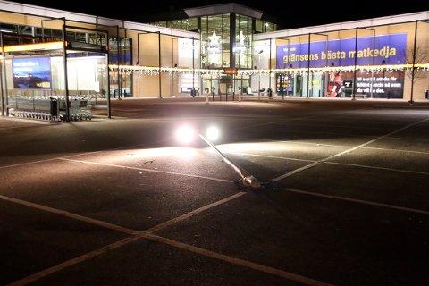 En brukket lysmast ligger på parkeringsplassen utenfor kjøpesenteret i Töcksfors i Sverige, der en norsk kvinne ble angrepet med øks og hennes mann truet med kniv, før ukjente personer stakk av med parets bil mandag kveld.