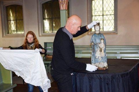 PAKKET UT: Eivind Bratlie og Pia Edqvist fra Kulturhistorisk museum ved Universitetet i Oslo brakte med seg madonnaskulpturen i en solid metallkasse, og pakket ut klenodiet med nennsom hånd i Eidsberg kirke tirsdag.