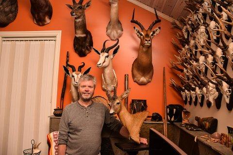 MANGE DYR: Trøgstingen Asbjørn Ness har vært over hele verden på jakt etter trofeer. Nå vil han felle en ny elg med en ung lokal jeger.