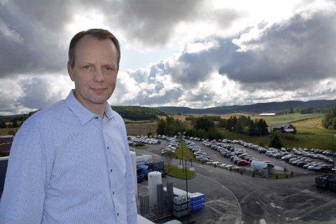 PARKERINGS-KAMP: Lars Ove Flaten på taket av Nortura-fabrikken. I bakgrunnen noe av parkeringsarealene til de ansatte, og hvor det til tider er kamp om plassene.