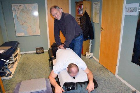 VED BENKEN: Hvor mange ganger Gunnar Bostrøm har inntatt denne arbeidsstillingen for å behandle folks ryggplager, har han selvsagt ikke noe tall på, men godt over 20.000 pasienter er registrert i kartoteket hans. For anledningen er kollega Sigve Tverodd i rollen som pasient.