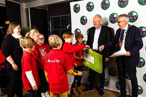 Daglig leder for Askim Entreprenør, Thor-Ole Riiser (midten), og Spydeberg-ordfører Petter Schou (H) deler ut penger til skolekorpset i Spydeberg.