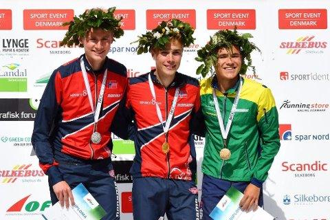 TOK GULL: Kasper Fosser (i midten) tok gull mandag i junior-VM i orientering. Rett etter på fikk han beskjed om at han også er tatt ut til O-VM i Spydeberg i august. Her sammen med Elias Jonsson og Anton Key (AUS).