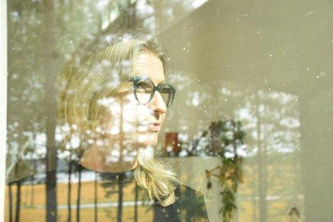 TILSLØRT: Ragnhild Vaaler Furulund i hjemmet ved Mosebyneset med Krokstadtjernet og Ørje i bakgrunnen. (For ordens skyld: Bildet er tatt gjennom stuevinduet, med Ragnhild på innsiden. Bakgrunnen speiler seg i vinduet.)