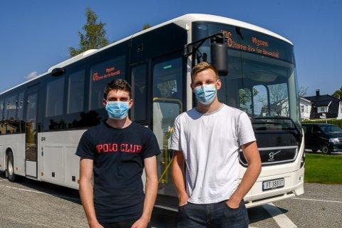 NY HVERDAG: Alexander Aaslie (t.v.) og Dziugas Markevicius forstår anbefalingen om å bruke munnbind på skolebussen. De to hadde sin første skoledag på Askim videregående skole mandag.
