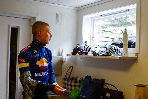 Eirik Lunder (19) tar en siste titt ut vinduet før han bestemmer seg for hvilken jakke han skal sykle med.