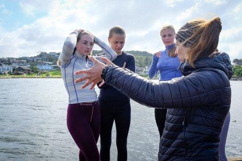 Lærer Katrine Sundve forklarer Emma Isabell Broadhurst (15), Anna Nordstrand (15) og Karoline Klepp (15) hvordan øvelsen i vannet skal foregå.