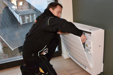 MONTERER: Asle Voster monterer varmepumpe i stua i det nye huset til Jone Heggheim og Andrea Sande på Tau.