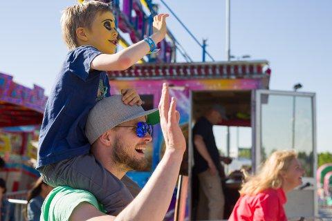 KJØRER KARUSELL: Sam og pappa Terje vinker til mamma og lillesøster som kjører karusell på Barnas dag. Foto: Christine Nevervik