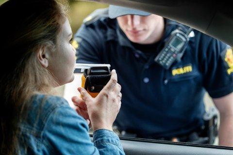 Politiet i arbeid. Politiet gjennomfører alko-testing med alkometer.