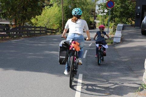 Hvis det ikke er adskilt sykkelfelt langs veien, er det lurt å legge seg litt bak og på utsiden av barnet. Da skjermer du barnet mot biler som kommer bakfra. Foto: NAF/ANB